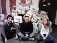 Team of students sitting with pile of boxes