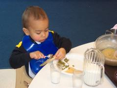 young child eats family-style meal at day-care center