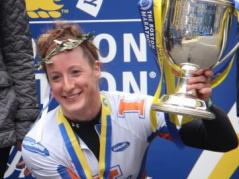 Tatyana McFadden holds up her first-place trophy at Boston Marathon