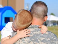 military family hugs preschool-aged son